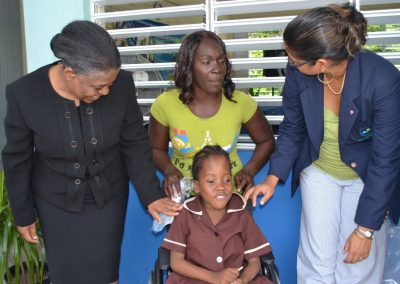 students receiving their wheelchairs from Karen McDonald Gayle (Chief Executive Officer of the EFJ-1