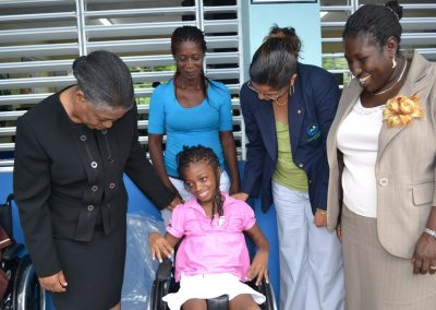 students receiving their wheelchairs from Karen McDonald Gayle (Chief Executive Officer of the EFJ-3